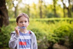 Little boy blowing soap bubbles Stock Photos