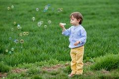 Little boy blowing soap bubbles Stock Photography