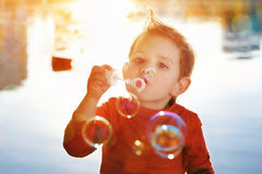 Little boy blowing soap bubbles stock images