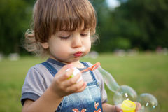 Little boy blowing soap bubbles Stock Images