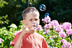 Little boy blowing soap bubbles Stock Photos
