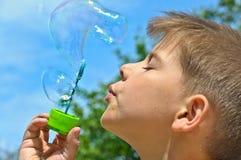 A little boy blows bubbles Royalty Free Stock Photo