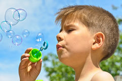 A little boy blows bubbles. Background sky Stock Photos