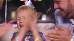 Little boy blows out candles on birthday cake stock video