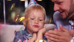 Little boy blows out candles on birthday cake stock video footage
