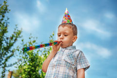 Little boy blows a party horn Royalty Free Stock Photography