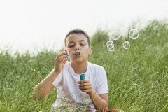 Little boy blows soap bubbles Royalty Free Stock Photo