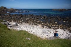 Little boy with blue backpack, sits on ground at irish coast rock, next to the sea stock images