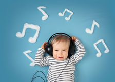Little boy on blue blanket background with headphones. Happy little boy on blue blanket background with headphones and musical notes on blue background Royalty Free Stock Photography