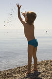 Little boy in blue cowards throws stone up. On a background marine horizon Royalty Free Stock Photography
