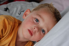 Little boy with blue eyes in bed. Three year old boy with big blue eyes in bed wth a sad expression, maybe a fever Stock Images
