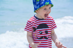 Little boy with blue eyes screaming with happiness on the beach, hamming, Stock Photos