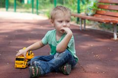 Little boy with blue eyes sits on the cover of children playground with a toy - yellow excavator. Blonde hair, thoughtful look, al. One. Casual jeans, aquamarine stock photos