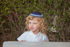 The little boy with blue eyes in skullcap. The charming little boy with blue eyes and long blond curls in Jewish knitted skullcap. Autumn holiday of Sukkot Stock Photo
