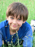 Little Boy Blue Green Field. Boy in blue t-shirt lying in a field of green grass/weeds; he is smiling, looking at the camera Stock Photo