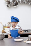 Little boy with blue hat and apron baking Royalty Free Stock Photos