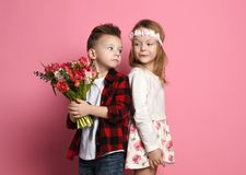 Little boy in blue jeans and red shirt is going to give a bouquet of spring flowers to little girl in dress add wreath of flowers. On pink background royalty free stock image