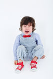 Little boy in blue jumpsuit sits on floor and cries. On white background Stock Images