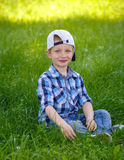 A little boy in a blue plaid shirt is sitting Royalty Free Stock Photo