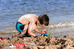 Little boy in blue sea Stock Photos