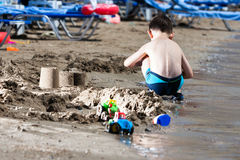 Little boy in blue sea and sand play. Little boy in blue sea playing with mud pies and sand stock photos