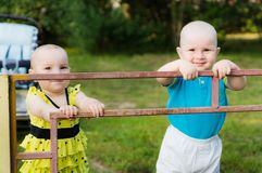 A little boy in a blue shirt and a girl in a yellow dress are standing behind an iron fence royalty free stock image