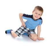 Little boy in a blue shirt and plaid shorts Stock Photo