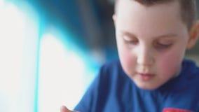 Boy eating dessert. Little boy in blue t-shirt eats dessert stock video