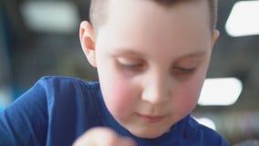 Boy eating dessert. Little boy in blue t-shirt eats dessert stock video footage