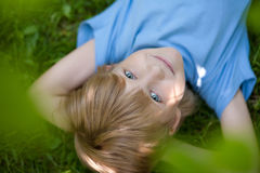 Little boy in blue t-shirt lying on the grass Royalty Free Stock Photo