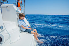 Little boy on board of sailing yacht on summer cruise. Travel adventure, yachting with child on family vacation. Cute boy on board of sailing yacht on summer stock photography
