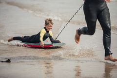Little Boy Body Boarding. Little boy being pulled along by his father at the beach on a body board Royalty Free Stock Photography