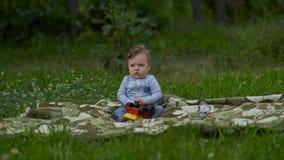 Little Boy bonito está jogando apenas no jardim