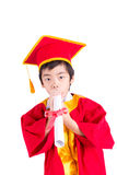 Little Boy bonito que veste a graduação vermelha da criança do vestido com barrete Foto de Stock