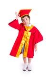 Little Boy bonito que veste a graduação vermelha da criança do vestido com barrete Foto de Stock Royalty Free
