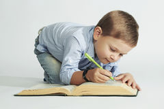 Little boy with book on the floor. funny child writer Stock Image