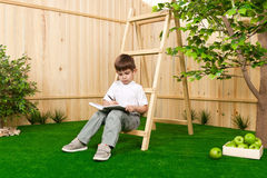 Little boy with a book in the garden stock photos