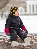 A little boy in boots sits on a large fallen tree in winter stock photo