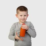 Little boy with bottle of orange carrot juice in hand royalty free stock image