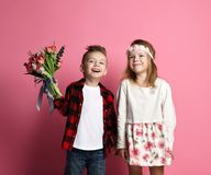 Little boy with a bouquet of spring flowers and little girl kid in wreath of flowers look at sky happy smiling. On pink background stock photography