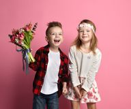 Little boy with a bouquet of spring flowers and little girl in pink spring dress and wreath of flowers laughting. On pink background with free text space stock photos
