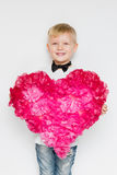 Little boy in bow tie shared a big heart from paper flowers stock image