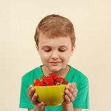 Little boy with bowl of fresh ripe strawberries Stock Photo