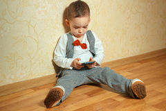 Little boy with bowtie playing mobile phone Royalty Free Stock Photography