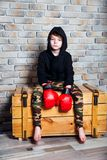 Little boy boxer with blonde hair dressing in black sweatshirt wearing boxing gloves posing in a studio. Young boxer .Little boy boxer with blonde hair dressing stock images