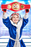 Little boy boxer holding Boxing championship belt. The athlete in scrubs in the background of the ring. Little champion. Boy boxer holding Boxing championship stock image
