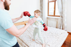 Little boy in boxing gloves playing with his dad Stock Image