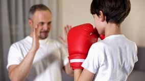 Little boy boxing with his step-father, learning attacking, family togetherness. Stock photo royalty free stock photography