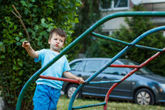 Little boy with branch on jungle gym Stock Photos