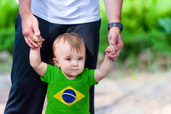 Little Boy in Brazil Flag shirt. Toddler in Brazil Flag shirt walking supported by his father stock image